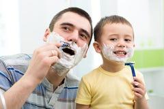 试图的小男孩刮象他的爸爸 免版税库存照片