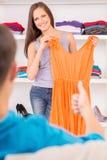 试穿新的礼服和微笑的妇女 免版税库存图片