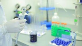 试管closeup.medical玻璃器皿 医疗设备 使用一根微吸移管的科学家的特写镜头英尺长度在实验室 实验室 免版税库存图片