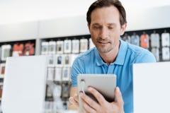 试验大模型数字式片剂的被聚焦的人在商店 免版税图库摄影