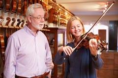 试验小提琴的顾客在音乐商店 免版税库存图片