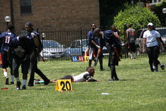 诚实的体育一运动员跌倒和其他帮助他起来 免版税库存图片