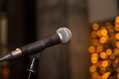 话筒在音乐厅或会议室有defocused bokeh的在背景中点燃 免版税库存图片