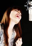 话筒妇女年轻人的唱歌工作室 库存图片