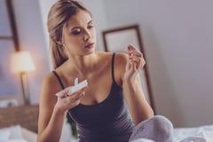详细检查镇痛药胶囊的俏丽的金发妇女 免版税库存图片