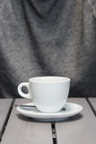 详述一个加奶咖啡杯子的射击在一张灰色木桌上的 免版税图库摄影