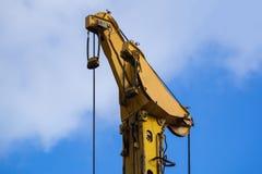 详述从一台黄色起重机的看法在蓝天前面 库存照片