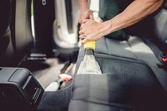详述和汽车保养概念-使用蒸汽真空的专家为排泄污点 免版税库存照片