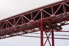 详述红色钢粱吊桥看法在阴云密布的 免版税库存照片