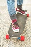 详述Longboard部分地大与一个女孩的腿运动鞋的 免版税库存照片