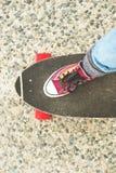详述Longboard部分地大与一个女孩的腿运动鞋的 库存图片