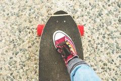 详述Longboard部分地大与一个女孩的腿运动鞋的 免版税库存图片