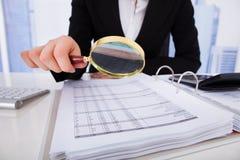 详细检查与放大镜的女实业家票据 免版税库存照片