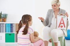语言矫治者和孩子 免版税库存图片