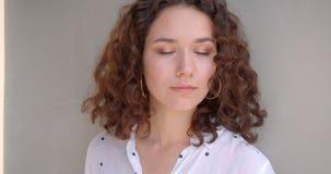 诱人地看照相机的年轻俏丽的长发卷曲白种人女性模型特写镜头画象有背景 股票录像