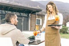 诱人的女服务员给顾客带来开胃酒 免版税库存照片