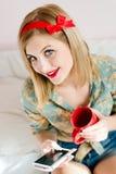 诱人,美丽的坐在与流动手机和红色杯子愉快微笑的床上的画报白肤金发的少妇蓝眼睛女孩 免版税库存照片