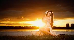 诱惑摆在室外在美好的日落前面的礼服的深色的白种人妇女。露出她的美丽的赤足女孩 免版税图库摄影
