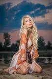 诱惑摆在美好的日落前面的透明女衬衫的华美的白肤金发的妇女 多云天空的公平的头发女孩 免版税图库摄影
