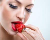 诱惑-美丽的妇女,当闭合的眼睛,采取草莓的叮咬 库存图片