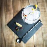 诱捕与botanicals的补品和在木桌上的酒吧匙子 免版税库存图片