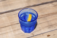 诱捕鸡尾酒用在一块蓝色玻璃的柠檬 免版税库存照片