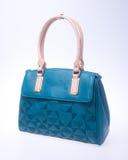诱饵 在背景的蓝色颜色时尚妇女袋子 库存图片