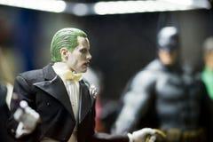 说笑话者字符可收回的模型和被弄脏的蝙蝠侠模型在背景 库存照片
