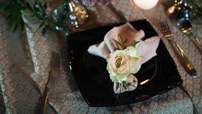 说谎一朵装饰花和餐巾的一个黑色的盘子,左右利器,在的桌布说谎 影视素材