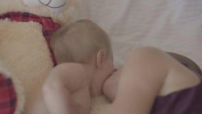 说谎与她的女婴和亲吻她的面颊在床上的美丽的年轻女人,出价的玩具熊是近 r 影视素材