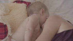 说谎与她的女婴和亲吻她的面颊在床上的美丽的年轻女人,出价的玩具熊是近 r 股票视频