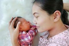 说谎与她的白色毛皮背景的儿子的亚裔母亲 婴孩和妈妈特写镜头  库存图片