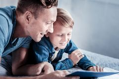 说谎和沟通与儿子的满意的宜人的父亲 库存照片