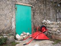 说谎在一个绿色门前面的地板上的红色独轮车 库存图片