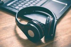说谎在一个膝上型计算机键盘的角落的黑无线顶上的耳机在办公室 库存照片