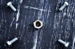说谎在一张木桌上的修理的坚果 铁坚果和螺丝f 免版税库存图片