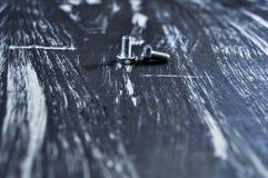 说谎在一张木桌上的修理的坚果 铁坚果和螺丝f 免版税库存照片