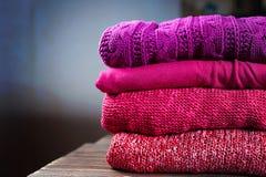 说谎在一张木桌上的堆温暖的编织的衣物 库存照片