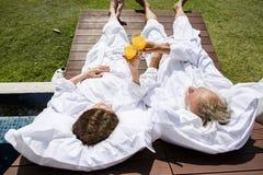 说谎在一张木海滩睡椅的老夫妇 库存照片