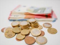 说谎在一张白色书桌上的欧元硬币和钞票混合物  各种各样的衡量单位纸币和硬币  免版税图库摄影
