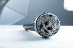 说谎在一张白色桌上的一个无线话筒 以演播室设备为背景,软的箱子 库存图片