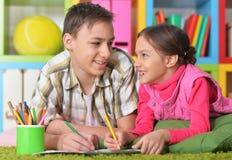 说谎在一张绿色地毯的兄弟和姐妹 免版税库存图片