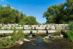 说谎在一条小河-水坝的具体块 免版税库存图片