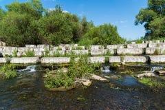 说谎在一条小河-水坝的具体块 库存照片