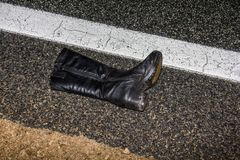 说谎在一条湿柏油路的妇女的起动在事故以后 免版税库存照片