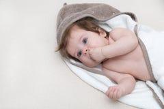 说谎在一条白色床毯子的逗人喜爱的女婴和在他的嘴保留手指 愉快童年的概念 婴孩吮 免版税库存图片