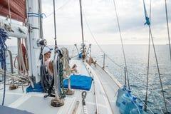 说谎在一条风船前面的甲板的男孩和女孩在加勒比海在Utila,洪都拉斯,中美洲附近 库存图片