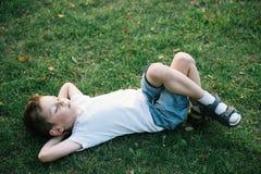 说谎在下落的叶子中的绿草的一个逗人喜爱的小男孩在公园 免版税图库摄影