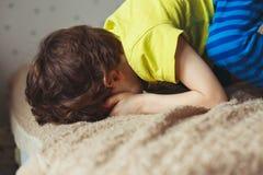 说谎在与下来他的面孔的床上的疲乏的小孩男孩 哭泣的小孩 免版税库存图片