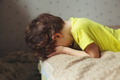 说谎在与下来他的面孔的床上的疲乏的小孩男孩 哭泣的小孩 免版税图库摄影